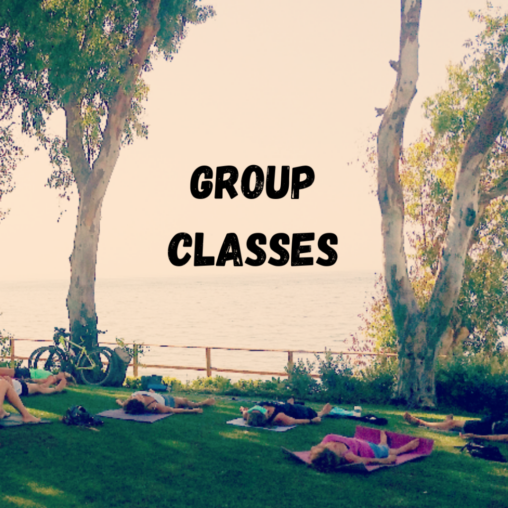 Savasana Yoga Pose on the grass under trees by the sea with text Group Classes